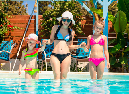 Photo pour Smiling mom with little daughters stand by holding hands and going to swim in the sunshine blue pool - image libre de droit