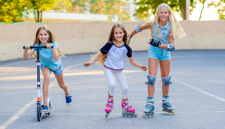 Photo pour Pretty smiling little girls compete riding in the skatepark at warm summer evening - image libre de droit