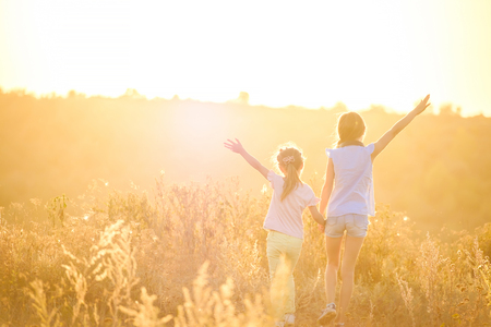 Photo for Little girls stand by holding hands looking on sunshine evening field with joyfully raised hands - Royalty Free Image