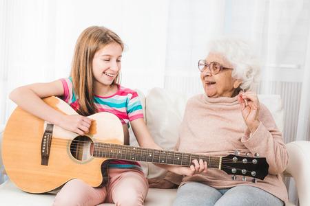 Photo pour Grandmother listening granddaughter playing guitar - image libre de droit