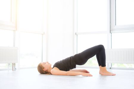 Photo pour Pretty young girl doing exercises on a floor in white room - image libre de droit