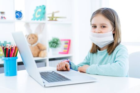 Photo pour Cute little girl studying at home during quarantine - image libre de droit