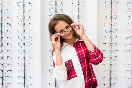 Photo pour Teenage girl with a black glasses standing in the optical store - image libre de droit