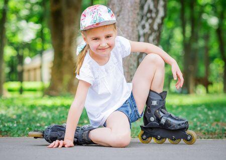 Photo pour Little smiling girl in roller skates in park - image libre de droit