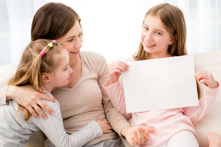 Photo pour Mother and daughters holding blank sheet of paper A4 in hands at home - image libre de droit