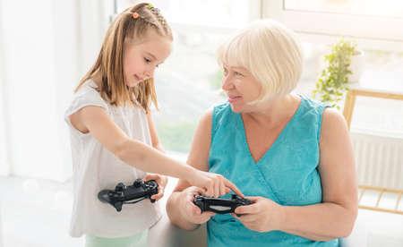 Photo pour Little girl teaching elderly woman to play on joystick indoors - image libre de droit
