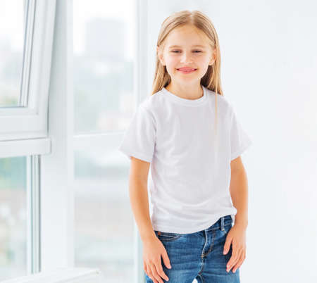 Photo pour Smiling little girl in simple white blank t-shirt - image libre de droit