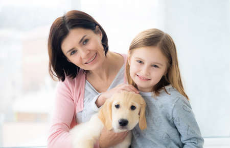 Photo for Sweet daughter and mother with lovely golden retriever dog - Royalty Free Image