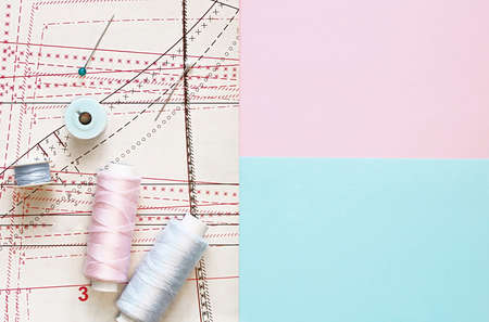 Multicolored thread coils on color background. Sewing supplies, pattern and accessories for needlework, stitching, embroidery. colour space for text. Flat lay, top view