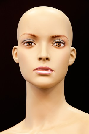 Face of a bald mannequin isolated on black background