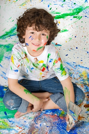 Adorable boy playing with the background painted