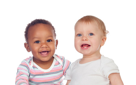 Photo pour Couple of Babies African and Caucasian laughing on white background - image libre de droit