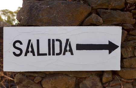 Poster with the word exit in Spanish and an arrow indicating the direction