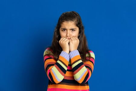 Adorable preteen girl with striped jersey on a blue background