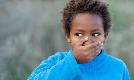 Photo pour Little african boy covering his mouth with a blue jersey - image libre de droit