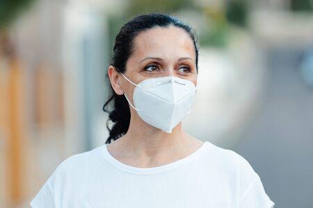 Photo pour Mature woman wearing a face mask on the street - image libre de droit