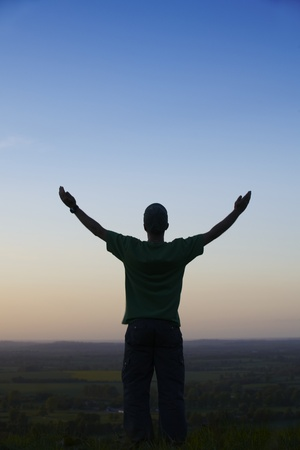 Man standing with arms outstretched in front of landscape at dusk