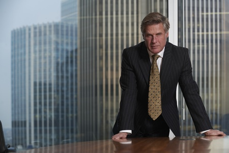 Photo pour Business man leaning on table in boardroom looking at camera - image libre de droit