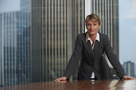 Photo pour Business woman leaning on chair in boardroom looking at camera - image libre de droit