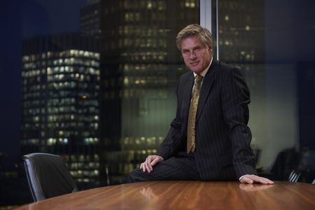 Photo pour Business man sitting on table in boardroom looking at camera - image libre de droit