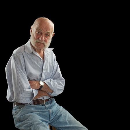 Elderly man looks interested, raises eyebrows, sits facing forward and crosses arms. He is bald with white mutton chop whiskers, wears jeans and open-collared shirt. Square composition, isolated on black, copy space.