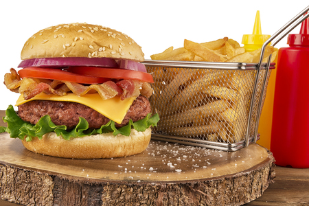 Photo pour Cheeseburger with beef patty and bacon. French fries in basket, ketchup and mustard bottle in background. Isolated on white background. Real close up. - image libre de droit