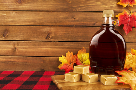 Foto per Maple syrup bottle on a wooden plank. Maple leaves in decoration. Copy space for your text. - Immagine Royalty Free