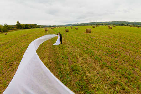 Bridegroom and bride with very long bridal veil on the background of green field and cloudy sky