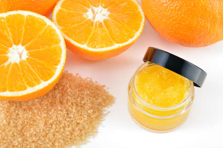 Natural orange sugar lip scrub on white background with reflection  Orange cosmetic in a glass jar with oranges in a background