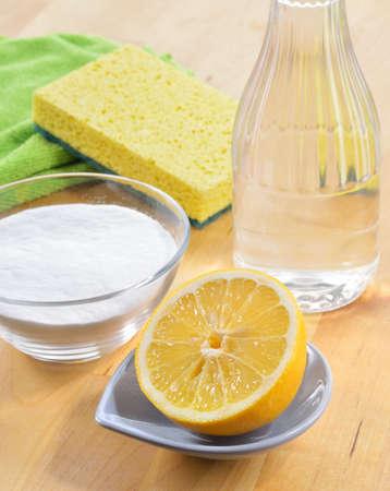 Vinegar, baking soda, salt, lemon and cloth on wooden table