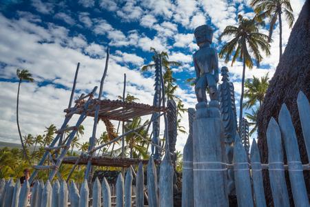 Old wooden structures and protection idols at ancient Hawaiian site Pu'uhonua O Honaunau National Historical Park on Big Island, Hawaii