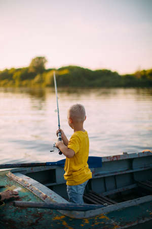 Photo for Baby boy fishing from boat on river in summertime, back view - Royalty Free Image