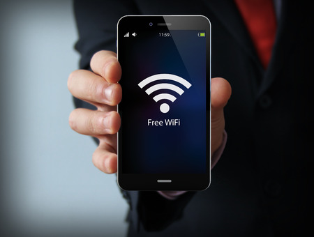 Photo pour business and mobility communications concept: businessman holding a modern smartphone with free wifi zone icon - image libre de droit