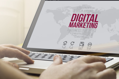 marketing digital concept: man using a laptop with computer generated digital marketing interface on the screen