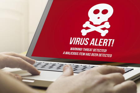 security concept: man using a laptop with virus alert on the screen. Screen graphics are made up.