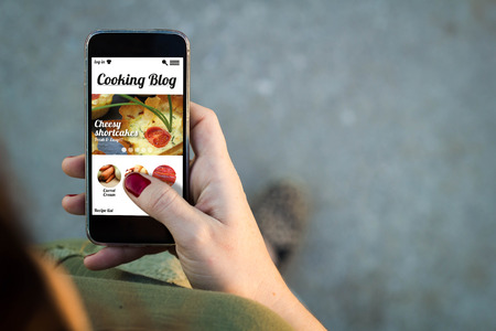 Top view of woman walking in the street using her mobile phone with cooking blog on screen.