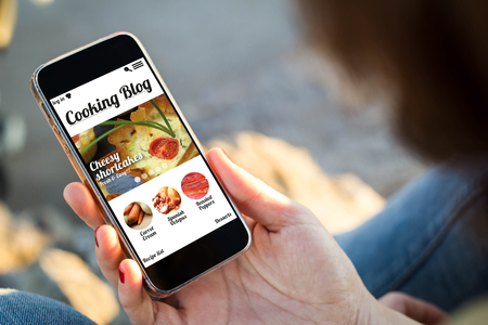 close-up view of young woman holding a smartphone with cooking blog on screen. All screen graphics are made up.の写真素材