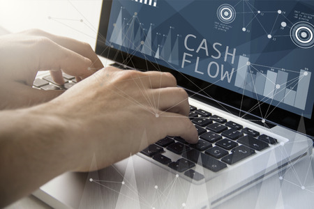 Photo pour technology and business concept: man using a laptop with cash flow software on the screen. All screen graphics are made up. - image libre de droit