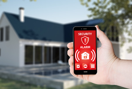 Hand hold a phone with security alarm app on a screen on the background of a house.