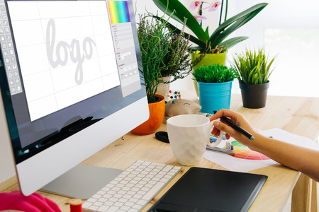 Graphic designer using pen tablet to design a logo. All screen graphics are made up.