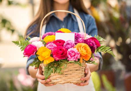 Photo pour Close-up. Young female florist holding bouquet of flowers in shop. Focus on bouquet. - image libre de droit