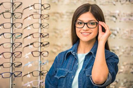 Photo pour Portrait of happy young woman buying a new glasses at optician store. - image libre de droit