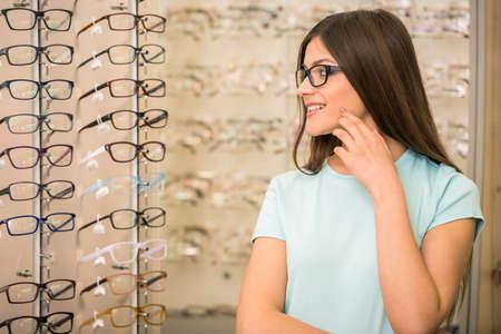 Photo pour Young woman is choosing a glasses in optician store. - image libre de droit