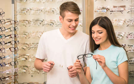 Photo pour Young couple at optician in the store, they looking for glasses. - image libre de droit
