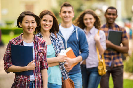 Foto de Group of young attractive smiling students dressed casual studying together in park. - Imagen libre de derechos