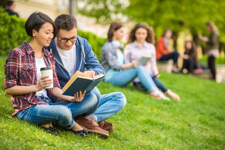 Foto de Couple of attractive smiling students dressed casual  studying outdoors on campus at the university. - Imagen libre de derechos