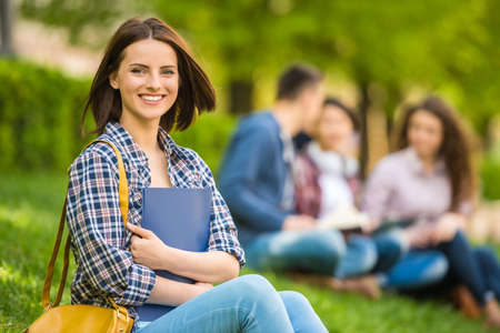 Foto de Young beautiful smiling student sitting on the lawn with friends and reading. - Imagen libre de derechos