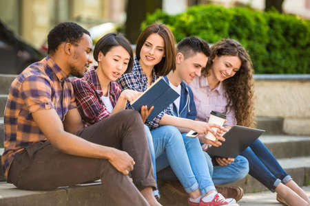 Photo pour Group of young attractive smiling students dressed casual sitting on the staircase outdoors on campus at the university. - image libre de droit