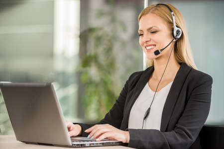 Beautiful young woman with headset sitting at office and using laptop.