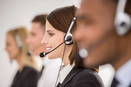 Photo pour Call centre workers working in line with their headsets. Side view. - image libre de droit